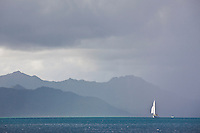 Sailboat about to be engulfed by a rain squall in lagoon of Raiatea