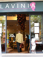 The entrance from the street with a giant bunch of grapes made from balloons and a sign saying Lavinia. A man businessman walking in with one hand in the pocket and the other hand carrying a briefcase. The Lavinia wine shop in Paris. Probably the biggest wine shop in Paris, with its special temperature controlled section for wines that are fragile and must be stored at cool low temperature.