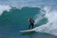A male surfer takes off down a wave
