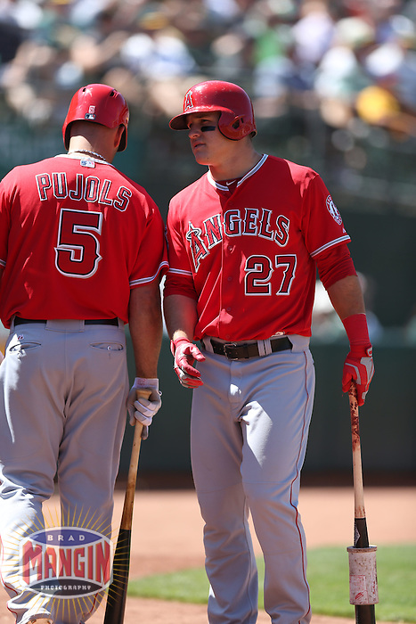 OAKLAND, CA - MAY 1:  Mike Trout #27 of the Los Angeles Angels talks with teammate Albert Pujols #5 during the game against the Oakland Athletics at O.co Coliseum on May 1, 2013 in Oakland, California. Photo by Brad Mangin
