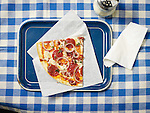 A large slice of pepperoni pizza on a blue tray with a parmesan cheese shaker and napkin. On a blue and white checkered restaurant tablecloth. Overhead view