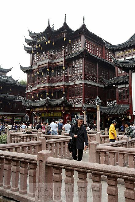 Tourists walk past traditional architecture in the Yuyuan Garden.<br />