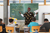 Switzerland. Canton Ticino. Barbengo. Elementary school. Don Gerald Chukwudi Ani is a catholic priest from Nigeria (Africa). He teaches religions' history to pupils. Wearing a boubou printed with lion's heads and a red hat, he stands in the classroom. On the backboard, he has drawn a dove, a colorful Eastern egg and written the words Pasqua (Eastern). Barbengo is a quarter of the city of Lugano. 23.03.2018 © 2018 Didier Ruef
