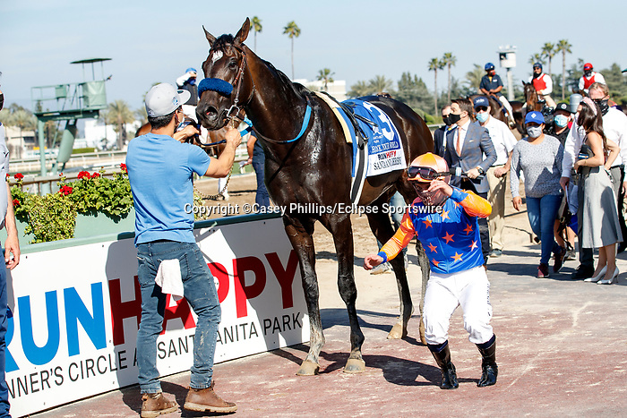 "ARCADIA, CA  APRIL 3:  Jockey Umberto Rispoli does a ""Frankie Dettori"" in the winners circle after winning the Santa Anita Derby (Grade l) on April 3, 2021 at Santa Anita Park, in Arcadia, CA.(Photo by Casey Pnillips/ Eclipse Sportswire/ CSM)"