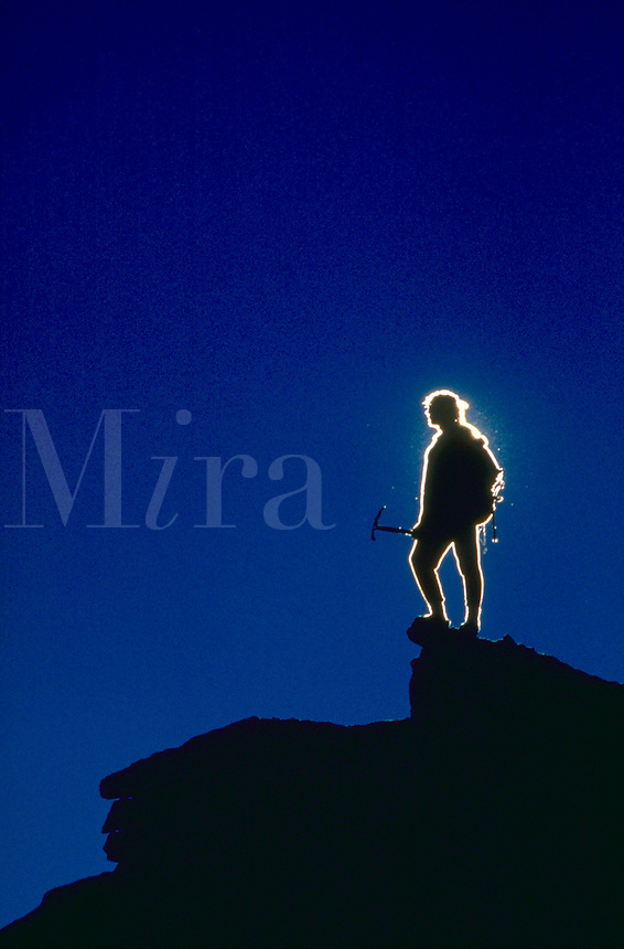 Climber silhouetted against a blue sky background, using a diffraction fringe technique, atop Mount Darwin in Kings Canyon National Park, California.