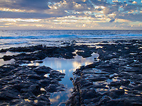 Pools of water along the Keahole coastline reflect the brilliant cloudy sunset on the Big Island.