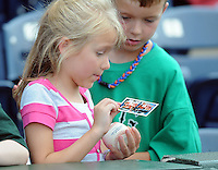 A young fan of the Greenville Drive shows off her autographed baseball card prior to a game against the Rome Braves on August 16, 2011, at Fluor Field at the West End in Greenville, South Carolina. (Tom Priddy/Four Seam Images)