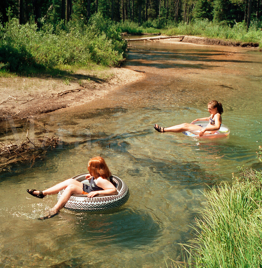 Young girls tubing a mountain stream..MR