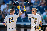 Michigan Wolverines first baseman Jimmy Kerr (15) is greeted at the plate by teammate Blake Nelson (10) after hitting a home run against the Texas Tech Red Raiders in the NCAA College World Series on June 21, 2019 at TD Ameritrade Park in Omaha, Nebraska. Michigan defeated Texas Tech 15-3 and will play in the CWS Finals. (Andrew Woolley/Four Seam Images)