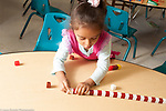 Education preschool 3-4 year olds making long row of cubes in a red and white pattern