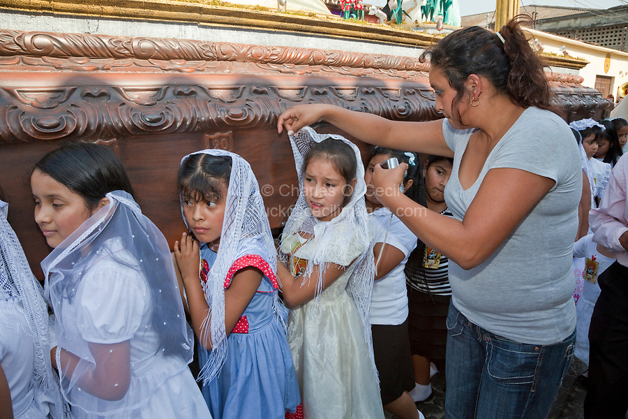 Antigua, Guatemala.  Semana Santa (Holy Week).  Mother Adjusting her Daughter's Lace Scarf as she Carries an Anda (Float) in a Religious Procession.