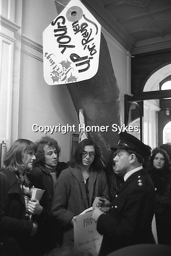 """Gay Liberation Front demonstration agains Dr David Reubens book published by Pan Books. central London 1971.   12-foot papier-mache cucumber was delivered to the offices of Pan Books in protest at Dr David Reuben's homophobic book, """"Everything You Always Wanted To Know About Sex"""", which suggested that all gay men were """"obsessed with shoving vegetables up their ..."""" Confront Pan Book security man in the lobby of their office."""
