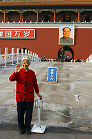 CHINA. Beijing.  An old woman stands in front of the famous Mao Zedong portrait that hangs on the 'Gate of Heavenly Peace' which leads into the Forbidden City and is opposite Tiananmen Square. Mao is still revered in China even 30 years after his death and 40 years since the end of the 'Cultural Revolution' and the 'Great Leap Forward' where it is alleged he was responsible for the death of some 20 million Chinese people. Nevertheless, every day thousands of Chinese people make the pilgrimage to stand and have their photo taken in front of his most famous portrait. 2005.