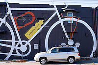 Picture of large bike with car in front