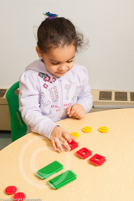 Education preschool 3-4 year olds girl arranging manipulative toys by geometric shape and color