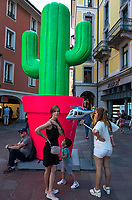 Switzerland. Canton Ticino. Lugano. Town center, A fake giant plastic cactus used as decoration for Longlake Festival stands on Piazza Alighieri Dante. A mother and her children stands by the cactus's red pot. The sun holds in his hands an inflated balloon with the shape of an helicopter. Manor and H&M shops. 23.07.2018 © 2018 Didier Ruef<br /><br /><br />.