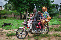 Nigeria. Enugu State. Agbani. St. Bartholomew's Catholic Church. An Igbo family (father, mother and four children) ride a motorcycle and returns home after the end of the religious service. The woman wears a head tie which is a women's cloth head scarf. The head tie is used as an ornamental head covering or fashion accessory, or for functionality in different settings. Its use or meaning can vary depending on the country and/or religion of those who wear it. The head tie is called gele in Nigeria. Reverend Father Gerald Chukwudi Ani is a catholic priest from the Diocese of Lugano (Ticino, Switzerland). Back in his homeland, he has organized at the church a Sunday mass to celebrate his 10th year anniversary of priesthood and the 5th year of his mother's death. 7.07.19 © 2019 Didier Ruef