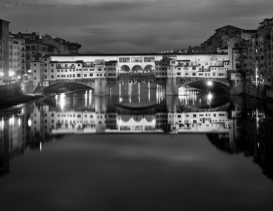 """""""The Glow of Ponte Vecchio""""<br /> Florence, Italy<br /> 2015<br /> <br /> The famous Ponte Vecchio Bridge is illuminated by the city lights in the predawn hours.  The medieval structure is noted for the many fine shops that are found on both sides of the pedestrian street.  Originally, the shops were occupied by butchers, tanners, and farmers.  This was the only bridge in Florence to survive WW II. <br /> <br /> 4 x 5 Large Format Film"""