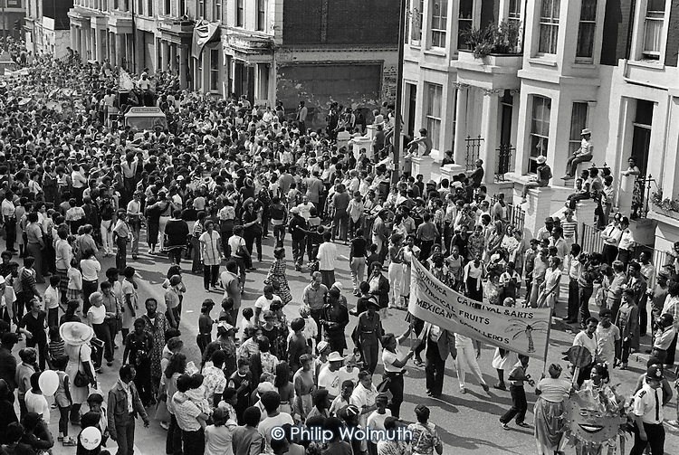 1980: a crowd in Westbourne Park Road during Notting Hill Carnival