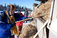 Volunteer helpers Debbie Koontz (L) of Galena and Janet Ross-Snyder (R) toss the straw  into a burn dumpster at the Galena checkpoint during the 2010 Iditarod