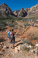 Red Rock Canyon, Nevada.  Hikers on Pine Creek Canyon Trail.  Mescalito Mountain (with red top) in center background.