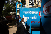A man drinks water from a bottle near government water trucks which deliver water to Latur's residents. The trucks often run throughout the day and into the night however many communities do not receive enough water and are forced to travel to government water facilities to retrieve more water themselves.