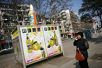 CHINA. Jiangxi Province.  Jiujiang. A woman next to advertisement advertising beer. Jiujiang is a city of 4.6 million people, located on the southern shore of the Yangtze River.  2008