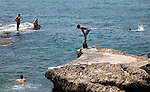 July 2010, LEBANON:  Swimmers on the rocks  near  the Hotel Saint George Yacht Club and Marina located on the Corniche on the shores of the Mediterranean Sea in Downtown Beirut.   Picture by Graham Crouch