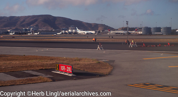 "Closure of runways 10R and 28L at San Francisco International airport (SFO), San Francisco, California.  In the background, an El Al 747 and San Bruno Mountain.  The fuel storage tanks in the background left spell ""SFO""."