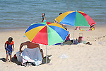 FAMILY RELAXES on the SEASHORE BENEATH BEACH UMBRELLAS