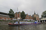Centraal Station and canal tour boat in Amsterdam, Netherlands.