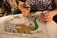 Local artisan painting a shahmaran, Mardin, Turkey. The mythical goddess is painted on glass
