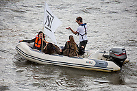 """The guy is a bit confused (t-shirt """"leave"""" and boat """"In"""")...<br /> <br /> London, 15/06/2016. Today, the River Thames outside the Houses of Parliament was the stage of an epic """"naval battle"""" between the """"Brexit Flotilla"""", lead by the UKIP leader Nigel Farage MEP, and the """"In Flotilla"""", lead by the Irish singer-songwriter Bob Geldof KBE. Nigel Farage MEP lead a flotilla of fishing trawlers from Southend in Essex sailing to the River Thames in front of the British Parliament to call for the UK's withdrawal from the EU and to repossess """"our water back"""". The protest and the counter protest were set to coincide with Prime Minister David Cameron question time.<br /> <br /> For more information about the """"Leave the EU"""" campaigns (for Brexit) please click here:  http://leave.eu/ & http://www.voteleavetakecontrol.org/<br /> <br /> For more information about the """"Remain In the EU"""" campaign (to stay in the EU) please click here: http://www.strongerin.co.uk/"""