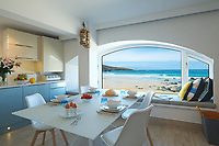 BNPS.co.uk (01202) 558833. <br /> Pic: KnightFrank/BNPS<br /> <br /> Pictured: The stunning view over Porthmeor Beach. <br /> <br /> The ultimate room with a view...<br /> <br /> A former fish cellar that is now an idyllic waterfront home overlooking a famous Cornish beach is on the market for £930,000.<br /> <br /> The ground floor apartment is in a prime frontline position with exceptional panoramic views over Porthmeor Beach and out to sea.<br /> <br /> Estate agent Christopher Bailey said the window in the reception space is like having your own live television screen looking out on the action of the beach.<br /> <br /> It has been designed and renovated to an exceptionally high standard and the immaculate flat is currently rented out for short holiday let, making about £40,000 profit a year.