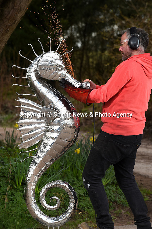 Pictured:  Sculptor Michael Turner working on his latest creations, grinding to shape and form a five and a half foot tall metal seahorse.<br /> <br /> Metal sculptor Michael Turner has found enquires for his services have increased by 60% during the lockdown period as people have focus on improving their garden and interior spaces around the home.<br /> <br /> The sculptor who has been busy throughout lockdown from his Lymington workshop in the New Forest, Hampshire believes the increase could be down to those who are usually able to treat themselves by going out, but are now looking to spend their money on items to improve their lockdown experience and surroundings.<br /> <br /> © Simon Czapp/Solent News & Photo Agency<br /> UK +44 (0) 2380 458800