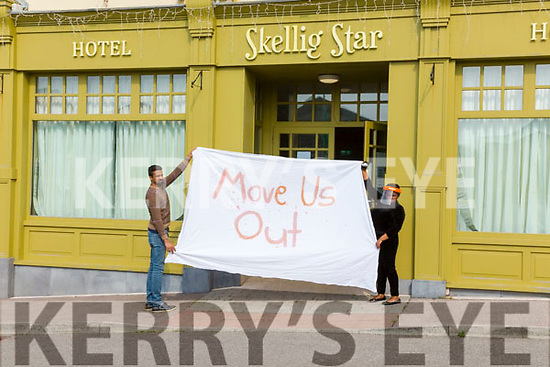 Two of the resident from the Skellig Star Direct Provision Centre in Cahersiveen on Saturday after the announcement that there were further cases of Covid-19 in the Centre holding a sign outside the building.