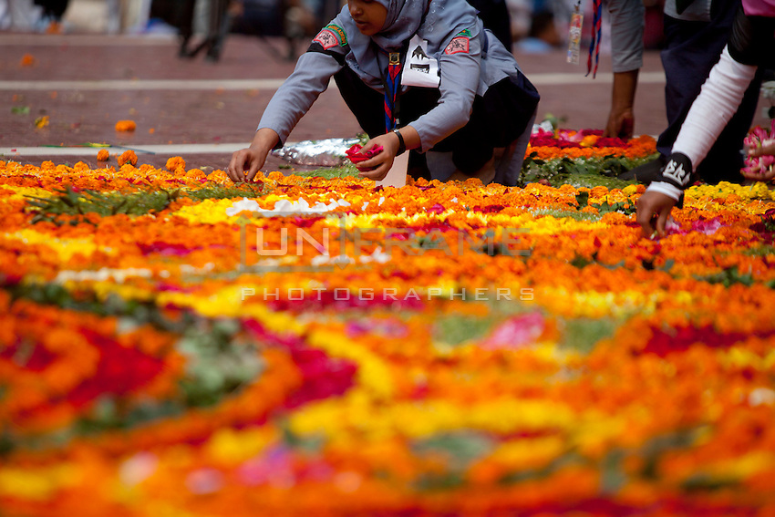 Bangladeshi girls decorates the Dhaka Central Shaheed Minar, or Martyr's Monuments on International Mother Language Day in Dhaka, Bangladesh, Saterday, Feb. 21, 2015. International Mother Language Day is observed in commemoration of the movement where a number of students died in 1952, defending the recognition of Bangla as a state language of the former East Pakistan, now Bangladesh. The day is now observed across the world to promote linguistic and cultural diversity and multilingualism.