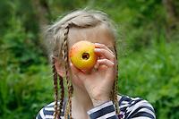 Mädchen guckt durch einen Apfel, bei dem das Kerngehäuse entfernt wurde
