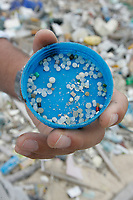 Nico Zurcher, a marine water quality management researcher at the University of Hong Kong, displays a sample of pre-production plastic pellets, or 'nurdles' found on the East-facing beach on the windward side of South Sokos Island, Hong Kong, China, 27 January 2010. South Sokos Island is one of a very small number of uninhabited islands in Hong Kong Special Administrative Region of China, and because it has no ferry service at all it is rarely visited by anyone. Consequently large amounts of marine-borne plastics build-up over time, with infrequent Hong Kong Government pollution clean-up efforts to tackle the problem. Common items found washed up on the beach at South Sokos Island include; lightbulbs, medical waste, plastic bottles, plastic cigarette lighters, plastic toys, plastic fishing equipment and plastic footwear. Another plastic item frequently found in large quantities on Soko Island, but also on polluted beaches the world over, is the pre-production plastic pellet, or 'nurdle', that is used in the manufacturing of plastic products. Toxic chemicals, such as PCBs (polychlorinated biphenyls), are known to concentrate in nurdles. The nurdles are then mistakenly eaten by fish who take them for food, and thus toxic chemicals end up entering the food chain, causing health problems in humans such as infertility and miscarriages, scientists say. ALEX HOFFORD