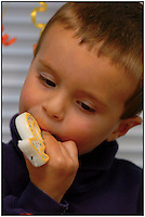 A boy licks the candle he just blew out on his birthday cake. Photo is part of a series of several images taken one after another. Model released photo.