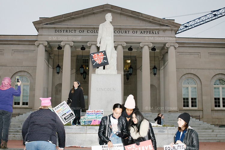 """A statue of Abraham Lincoln on E Street outside the District of Columbia Court of Appeals holds a protest sign reading """"I'm With Her"""" after the 2017 Women's March on Washington in Washington DC on Jan. 21, 2017."""