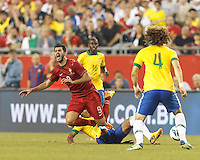 """Portugal forward Nelson Oliveira (9) goes down after """"all ball"""" slide tackle. In an international friendly, Brazil (yellow/blue) defeated Portugal (red), 3-1, at Gillette Stadium on September 10, 2013."""