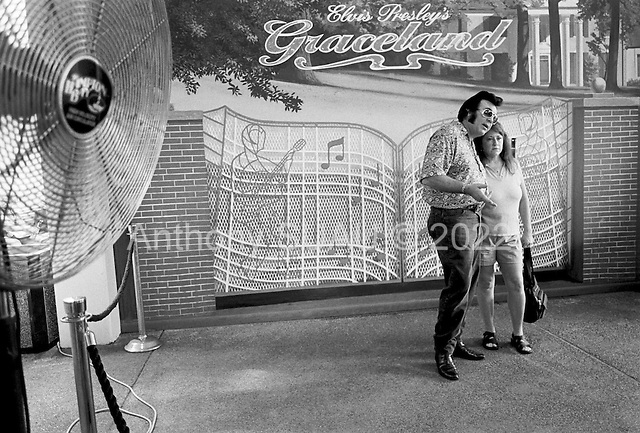 Memphis, Tennessee<br /> USA<br /> August 14, 2002<br /> <br /> Before boarding a bus into Graceland Elvis fans pose before a mural of the gates of Graceland. Thousands of fans from around the world visited the site during Elvis week which marked the 25th anniversary of the King's death.