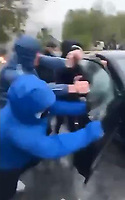 """Pictured: Young people pull a car off a Vauxhall Astra in Waun-Wen Road in the Mayhill area of Swansea, Wales, UK. Thursday 20 May 2021<br /> Re: Gangs of """"yobs"""" have been setting fire to cars and rolling them down a hill in Swansea, Wales, UK.<br /> South Wales Police said they attended """"large scale disorder"""" in the Mayhill area of the city on Thursday evening."""