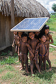 Ngoiwere Village, Mato Grosso State, Brazil. Kisedje (Suya); children with body paint playing under the shade of the solar panel, used for the radio (communications).