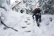 Hikers climb snow covered trail ladders on the Willey Range Trail in the White Mountains, New Hampshire USA during the winter months.