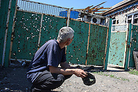 A man near the fence of his house pierced with shelling shrapnel, Donetsk, Eastern Ukraine, 20 May, 2015