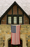 An American Flag hangs from a home in the Myers Park neighborhood in Charlotte, NC. Myers Park is one of the premier neighborhoods in North America and known for its large canopy of trees.