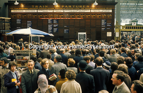 Waterloo main line train station 1972. Evening rush hour train commuters wait for information due to delays. London England.