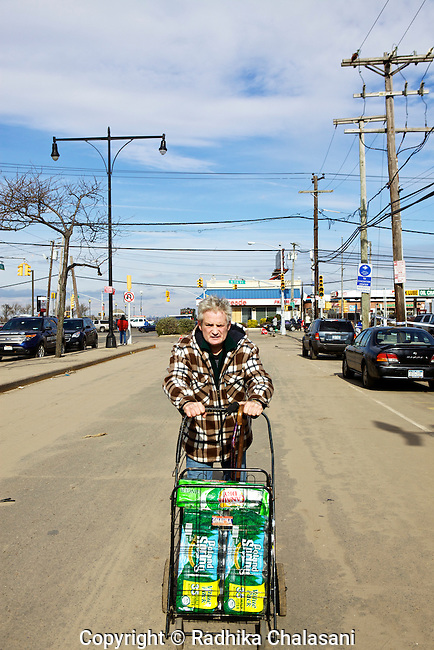 ROCKAWAY PARK, NEW YORK-NOVEMBER 01: A resident of Rockaway carries water given out for free at a Duane Reede store after Hurricane Sandy November 1, 2012 in this Queens neighborhood devastated by the storm. A large number of homes and businesses were destroyed and much of the area is without power.